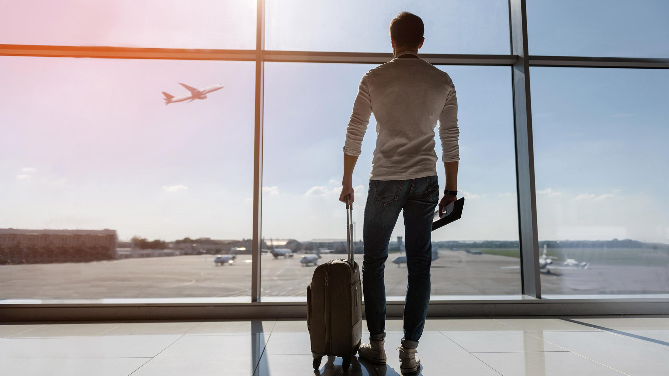 Jovem olha para um avião através da janela do aeroporto