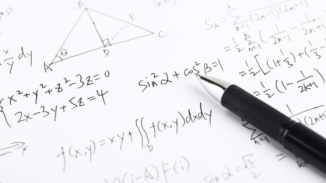 Close up de formulas matemáticas num papel e uma caneta sobre ele