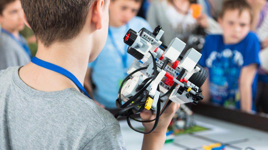 Sala com vários jovens à volta de uma mesa de trabalho com um jovem em primeiro plano a segurar um robot.