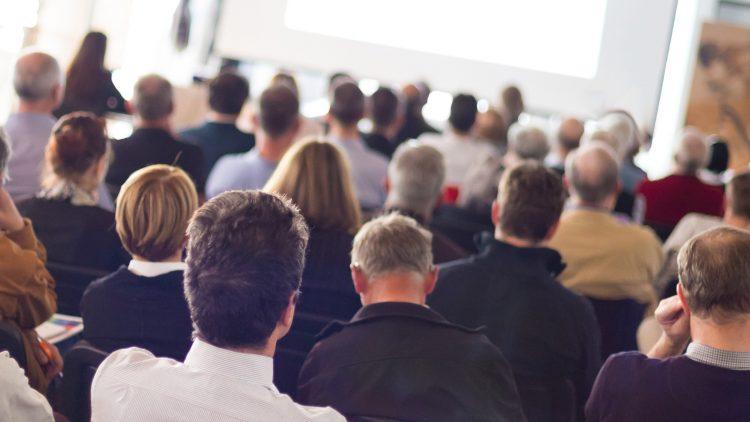 Público a assistir a um seminário com o palco visível ao fundo.