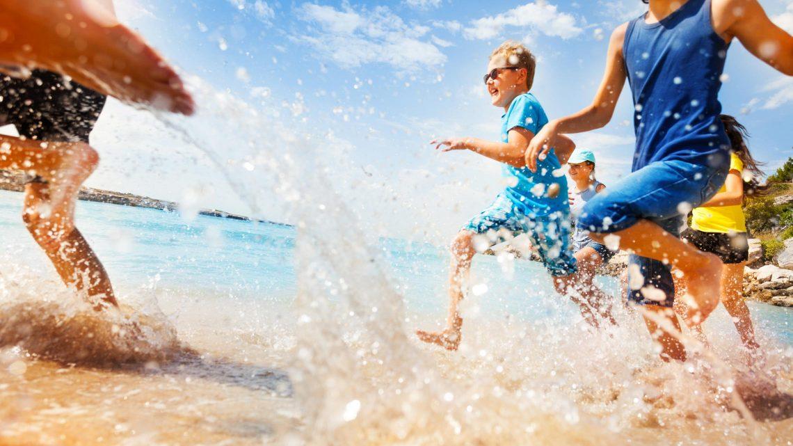 Crianças a divertirem-se e a correr na praia junto à água