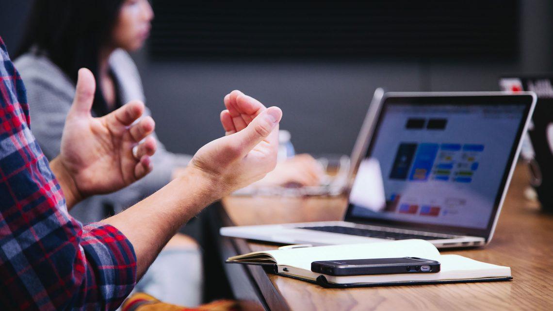 Close-up de um caderno e telemóvel em cima da mesa enquanto uma pessoa apresenta as suas ideias