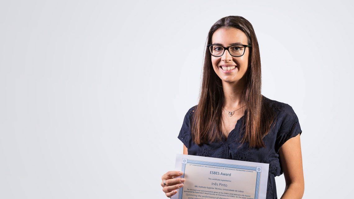 Inês Pinto a segurar o certificado atribuído pela Sociedade Europeia de Ciências de Engenharia Bioquímica