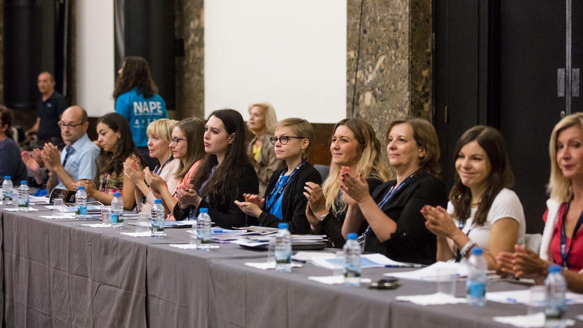 Participantes do International Staff Week sentados à mesa e a aplaudir
