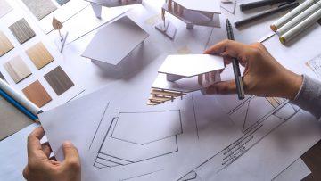 Arquiteto a comparar esboço desenhado em papel com modelo em baixa escala